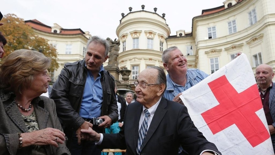 Former German Foreign Minister Hans-Dietrich Genscher, center, and his spouse Barbara Schmidt Genscher, left, meet with refugees from former Eastern Germany at the German embassy in Prague, Czech Republic, Tuesday, Sept. 30, 2014, during celebrations of the 25th anniversary of the exodus of East Germans. East Germans who sought refuge at the West German embassy in Prague were told by Genscher that they were allowed to go west shortly before the 1989 wave of anti-communist revolutions. (AP Photo/Petr David Josek)