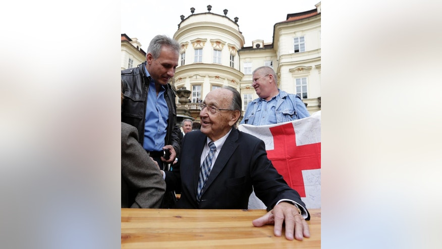 Former German Foreign Minister Hans-Dietrich Genscher, center, meets with refugees from former Eastern Germany at the German embassy in Prague, Czech Republic, Tuesday, Sept. 30, 2014, during celebrations of the 25th anniversary of the exodus of East Germans. East Germans who sought refuge at the West German embassy in Prague were told by Genscher that they were allowed to go west shortly before the 1989 wave of anti-communist revolutions. (AP Photo/Petr David Josek)