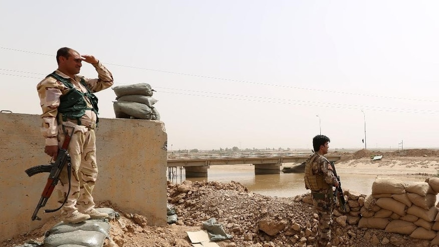 Kurdish Peshmerga fighters stand guard with their weapons as they patrol the front line with the Islamic State group near the Rashad Bridge, which connects the provinces of Salah al-Din and Kirkuk, 290 kilometers (180 miles) north of Baghdad, Iraq, Monday, Sept. 29, 2014. (AP Photo/Hadi Mizban)