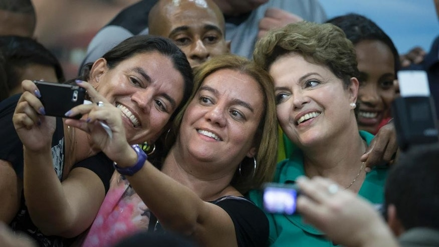Brazil's President Dilma Rousseff, right, who is running for reelection with the Workers Party (PT), poses for selfie photos with supporters after a meeting with athletes as she campaigns in Rio de Janeiro, Brazil, Tuesday, Sept. 30, 2014. Brazil will hold general elections on Oct. 5. (AP Photo/Felipe Dana)
