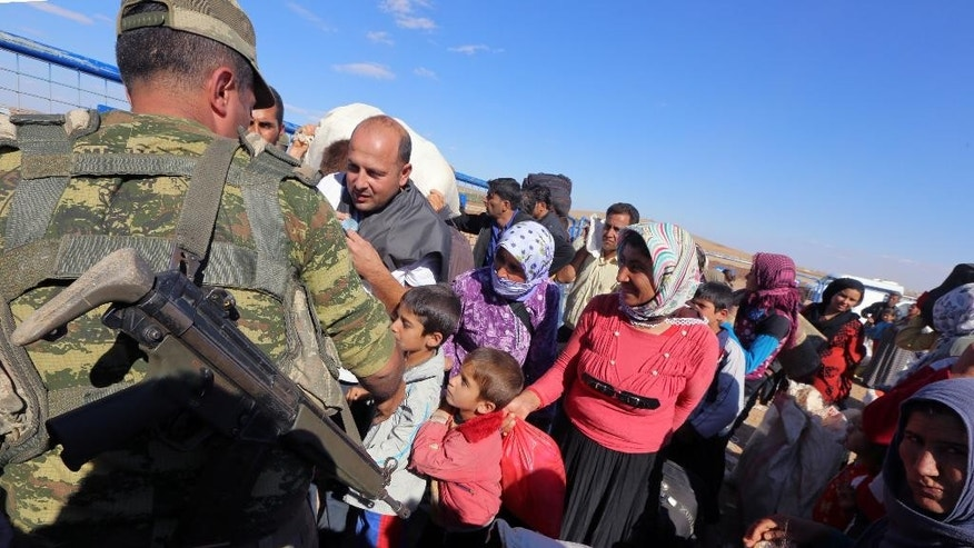 Syrian refugees arrive at the Turkey-Syria border near Suruc, Turkey, Tuesday, Sept. 30, 2014. U.S.-led coalition airstrikes targeted Islamic State fighters pressing their offensive against a Kurdish town near the Syrian-Turkish border on Tuesday in an attempt to halt the militants' advance, activists said. (AP Photo/Burhan Ozbilici)