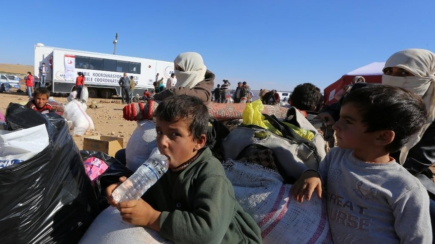 Syrian refugees wait for transport after their  arrival at the Turkey-Syria border near Suruc, Turkey, Tuesday, Sept. 30, 2014. U.S.-led coalition airstrikes targeted Islamic State fighters pressing their offensive against a Kurdish town near the Syrian-Turkish border on Tuesday in an attempt to halt the militants' advance, activists said. (AP Photo/Burhan Ozbilici)