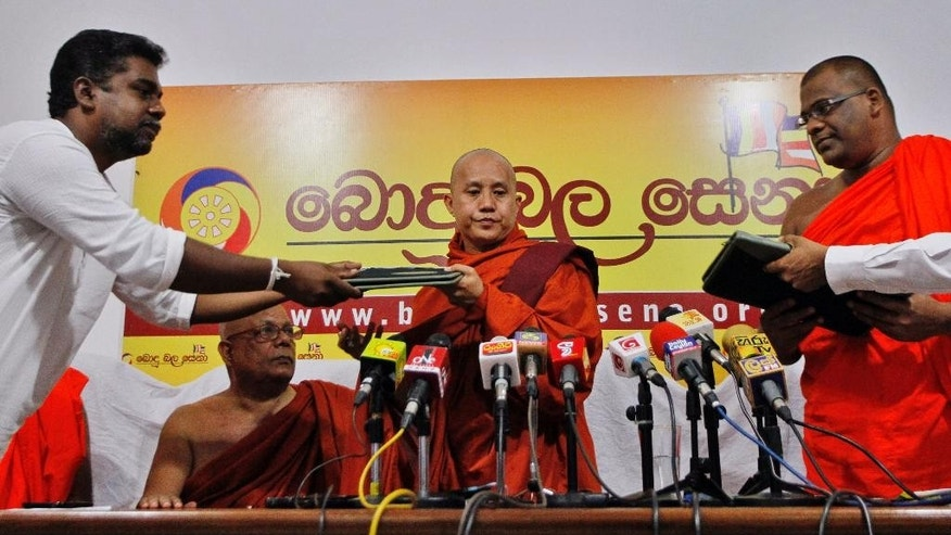 Myanmar's radical Buddhist monk Ashin Wirathu, center, exchanges copies of a three-point agreement with the officials of Sri Lanka's Bodu Bala Sena or Buddhist Power Force during a media briefing in Colombo, Sri Lanka, Tuesday, Sept. 30, 2014. Wirathu, known for his anti-Muslim campaign, has formalized an agreement with a like-minded Sri Lankan group to work together to protect Buddhism which he says is challenged worldwide. (AP Photo/Eranga Jayawardena)