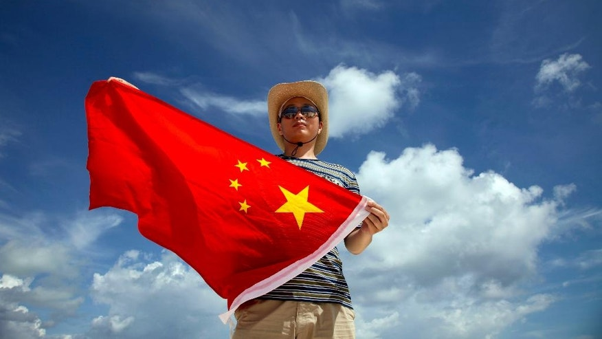 """In this Sept. 14, 2014 photo, Zhang Jing, a police officer poses with a Chinese national flag on the Quanfu island, a Paracels of Sansha prefecture of China's Hainan province. """"This is the southern frontier of China,"""" Zhang said when he had reached one of the islands. """"As a Chinese, I feel proud to come here and declare sovereignty."""" (AP Photo/Peng Peng)"""