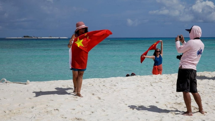In this Sept. 14, 2014 photo, Chinese tourists take souvenir photos with Chinese national flag as they visit to Quanfu island, a Paracels of Sansha prefecture of China's Hainan province. A cheer erupted on board at the sight of the distant land, and passengers scurried to take pictures of each other at the railing holding China's bright red flag. (AP Photo/Peng Peng)