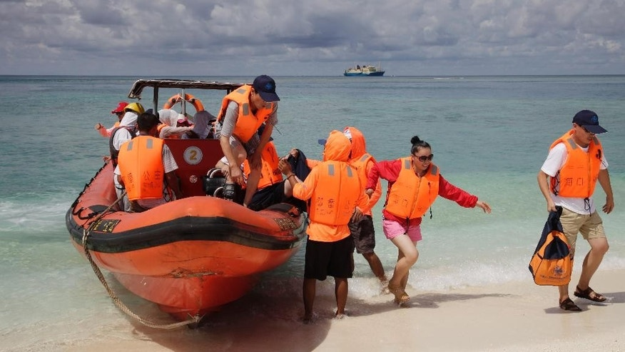 In this Sept. 14, 2014 photo, Chinese tourists disembark from an inflatable boat upon arrival in Quanfu island, a Paracels of Sansha prefecture of China's Hainan province. They had each waited months for permission to join the tour and then spent from $1,200 to about $2,000 to visit these barren patches of sand in the South China Sea, making do with the bland cabbage and noodles on board and blackouts of cellphone service. (AP Photo/Peng Peng)