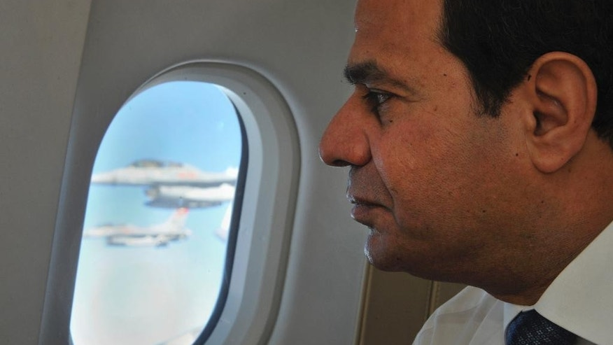 In this photo provided by Egypt's state news agency MENA, Egyptian President Abdel-Fattah el-Sissi looks out as air force jets escort the presidential airplane after it entered Egyptian airspace, Friday, Sept. 26, 2014. El-Sissi returned to Egypt from New York Friday after he addressed the 69th session of the United Nations General Assembly, at U.N. headquarters on Wednesday. (AP Photo/MENA)