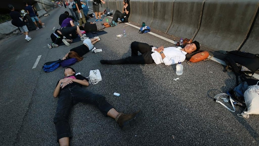Student activists sleep on a road near the government headquarters where pro-democracy activists have gathered and made camp, Tuesday, Sept. 30, 2014 in Hong Kong. Students and activists, many of whom have been camped out since late Friday, spent a peaceful night singing as they blocked streets in Hong Kong in an unprecedented show of civil disobedience to push demands for genuine democratic reforms. (AP Photo/Wong Maye-E)