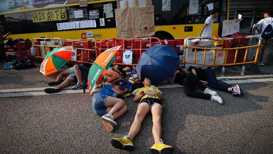 Student activists sleep in the shade of umbrellas, on a road near the government headquarters where pro-democracy activists have gathered and made camp, Tuesday, Sept. 30, 2014, in Hong Kong. Students and activists, many of whom have been camped out since late Friday, spent a peaceful night singing as they blocked streets in Hong Kong in an unprecedented show of civil disobedience to push demands for genuine democratic reforms. (AP Photo/Wong Maye-E)