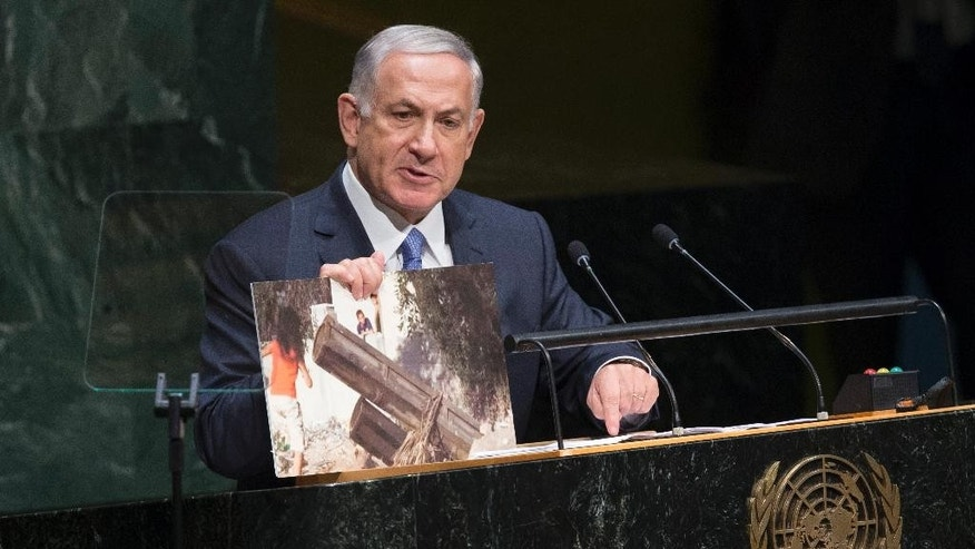 FILE -  In this Monday, Sept. 29, 2014 file photo, Israel's Prime Minister Benjamin Netanyahu displays a photo he says shows rocket launchers placed in residential neighborhoods of Gaza, as he addresses the 69th session of the United Nations General. In a pair of fiery speeches at the United Nations, the Israeli and Palestinian leaders appear to have abandoned any hope of reviving peace talks and instead seem intent on pressing forward with separate diplomatic initiatives that all but ignore each other. Both plans offer novel attempts at breaking months of deadlock, yet both appear doomed to fail. (AP Photo/John Minchillo, File)