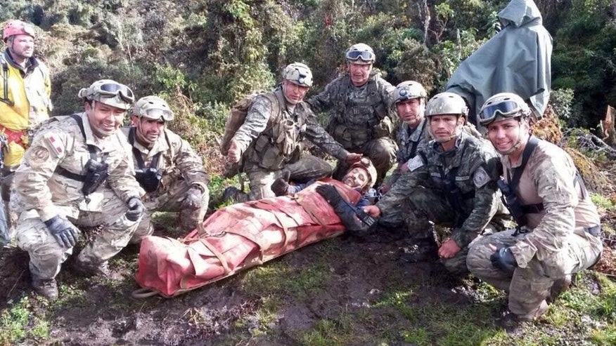 In this photo released by the Peruvian Air Force, officers pose for the picture with Spanish speleologist Cecilio Lopez after his rescue from inside the Inti Machay cave, in Leimebamba, Peru, Tuesday, Sept. 30, 2014. Lopez, a well-known cave explorer, was hurt when he fell inside the Inti Machay cave, where he remained trapped underground for 12 days in Peru's remote Amazon region. (AP Photo/Peruvian Air Force)