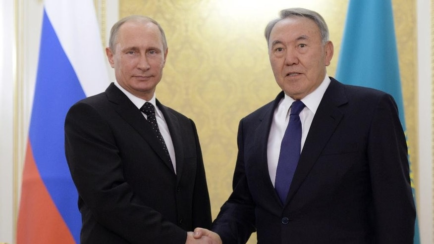 Kazakhstan's President Nursultan Nazarbayev, right, and visiting Russian President Vladimir Putin shake hands prior to their Kazakh-Russian talks in Atyrau, Kazakhstan on Tuesday Sept. 30, 2014. (AP Photo/RIA Novosti, Alexei Nikolsky, Presidential Press Service)