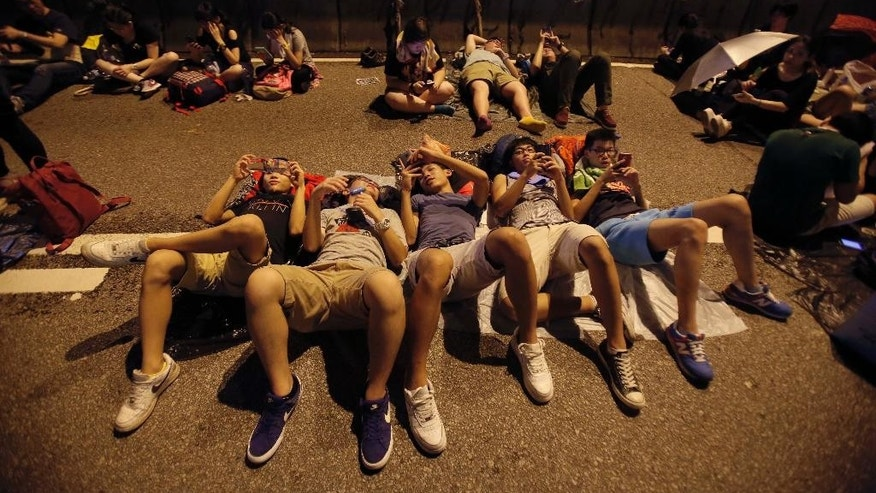 Student protesters rest as thousands occupy a main thoroughfare in Hong Kong, late Tuesday, Sept. 30, 2014. Hong Kong's leader refused to meet with pro-democracy demonstrators by their midnight deadline Tuesday, despite their threats to expand the protests that have clogged the streets with tens of thousands of people in the stiffest challenge to Beijing's authority since China took control of the former British colony in 1997. (AP Photo/Wally Santana)