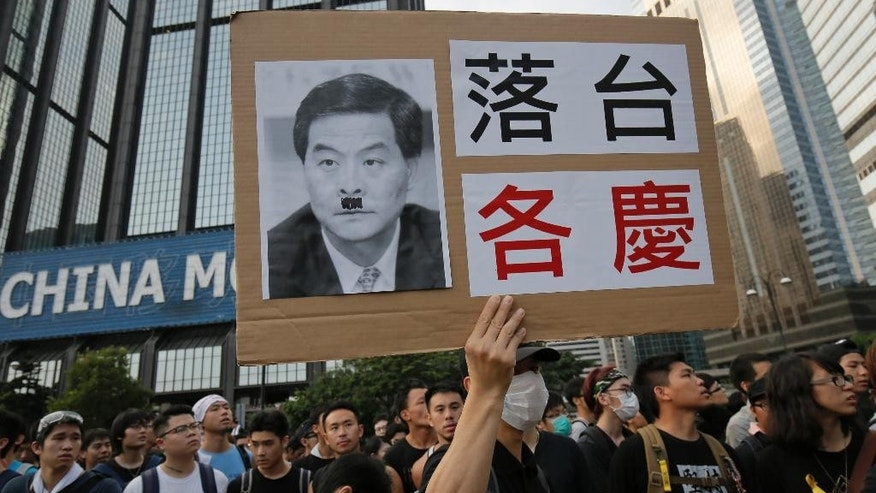 "Protesters raises a placard with a deface picture of Hong Kong's Chief Executive Leung Chun-ying outside a flag-raising ceremony where Hong Kong's embattled leader attended in Hong Kong, Wednesday, Oct. 1, 2014, to mark China's National Day. Leung attended the flag-raising ceremony Wednesday to mark China's National Day after refusing to meet pro-democracy demonstrators despite their threats to expand the street protests that have posed the stiffest challenge to Beijing's authority since China took control of the former British colony in 1997. The Chinese words read "" Step Down "" (AP Photo/Vincent Yu)"