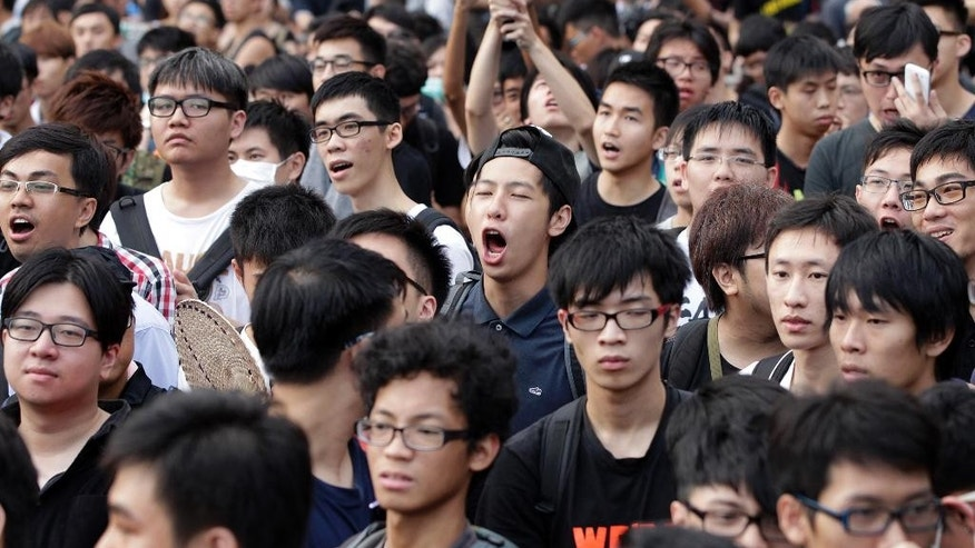 Student protesters chant anti-government slogans outside of the China's National Day flag raising ceremony in Hong Kong, Wednesday, Oct. 1, 2014. Hong Kong's embattled leader attended a flag-raising ceremony Wednesday to mark China's National Day after refusing to meet pro-democracy demonstrators despite their threats to expand the street protests that have posed the stiffest challenge to Beijing's authority since China took control of the former British colony in 1997. (AP Photo/Wally Santana)