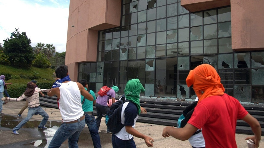 Students from a rural teachers college throw rocks at the State Congress building in Chilpancingo, Mexico, Sept. 29, 2014.