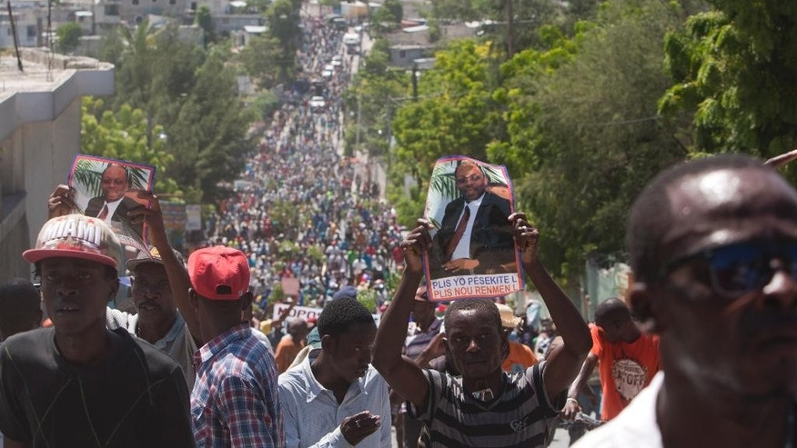 Supporters of former Haitian President Jean-Bertrand Aristide hold up pictures of him on the anniversary of the 1991 military coup that ousted Aristide, the country's first democratically elected leader, in Port-au-Prince, Haiti, Tuesday, Sept. 30, 2014. The march Tuesday marked the date that the military ousted Aristide less than a year into his first term as president. It also comes amid fears he will be arrested for failing to heed a court summons to testify in a corruption case. (AP Photo/Dieu Nalio Chery)