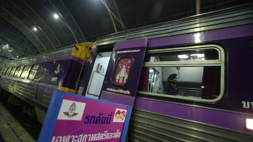 In this Sept. 29, 2014 photo, a female railway police officer checks the train carriages for women and children, at Hua Lamphong train station in Bangkok, Thailand, The State Railway of Thailand introduced a women's-only carriage on main routes for overnight trains following the rape and murder of a 13-year-old girl on an overnight train in July.(AP Photo/Sakchai Lalit)