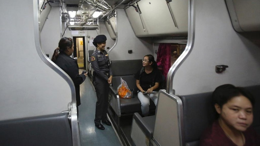 In this Sept. 29, 2014 photo, female railway police officers talk with a passenger at a train carriage for women and children, at Hua Lamphong train station in Bangkok, Thailand, The State Railway of Thailand introduced a women's-only carriage on main routes for overnight trains following the rape and murder of a 13-year-old girl on an overnight train in July.(AP Photo/Sakchai Lalit)