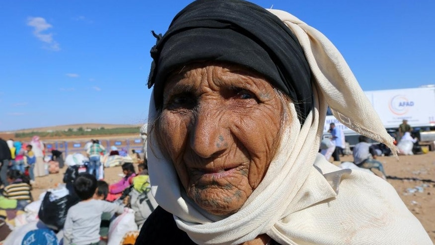 An elderly woman looks around as Syrian refugees arrive at the Turkey-Syria border near Suruc, Turkey, Tuesday, Sept. 30, 2014. U.S.-led coalition airstrikes targeted Islamic State fighters pressing their offensive against a Kurdish town near the Syrian-Turkish border on Tuesday in an attempt to halt the militants' advance, activists said. (AP Photo/Burhan Ozbilici)