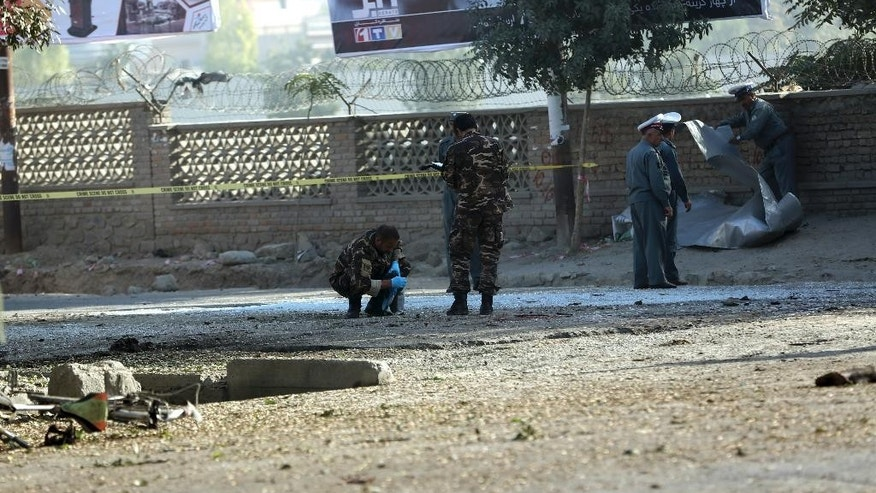 Afghan security forces inspect the site of a suicide attack in Kabul, Afghanistan, Wednesday, Oct. 1, 2014. Two suicide bombers in the Afghan capital targeted two buses carrying Afghan army troops on Wednesday, killing several people and wounding over a dozen, police said. (AP Photo/Massoud Hossaini)