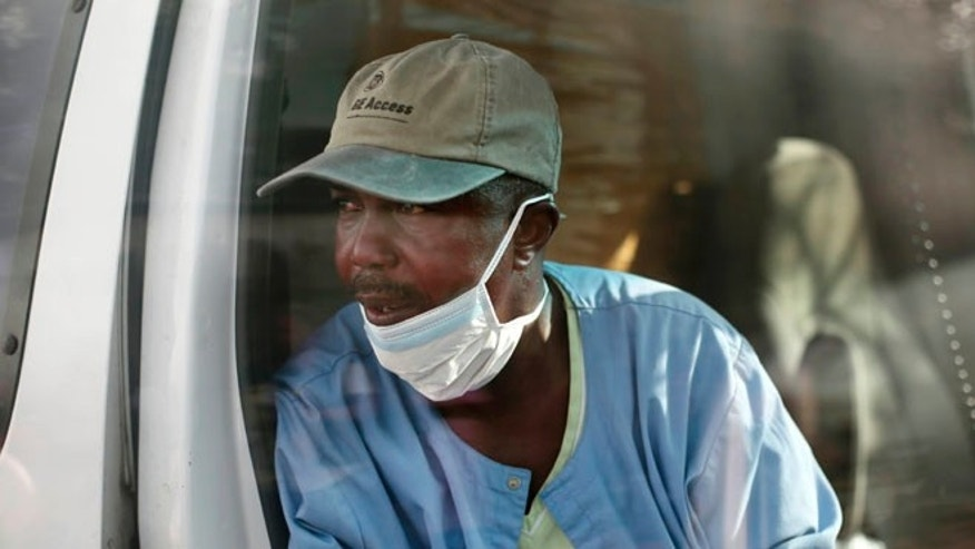 Sept. 30, 2014: Gordon Kamara, from the  District 13 ambulance  service, arrives at the Island Clinic Ebola treatment unit with six patients showing signs of Ebola