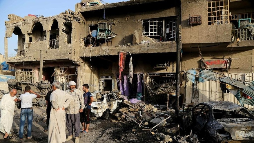 Oct. 1, 2014: Civilians inspect the site of double car bombings in the northern Shiite district al-Hurriyah in Baghdad, Iraq. On Tuesday, officials say a wave of bombings targeted commercial areas across Iraq, killing and wounding dozens of people.