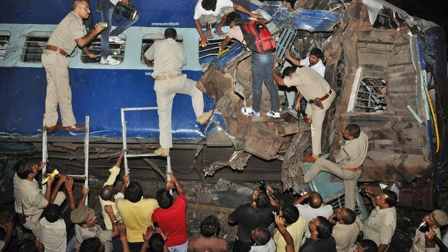 In this Sept. 30, 2014 photo, Indian policemen and workers try to rescue passengers from a damaged train near Gorakhpur city, India. A train overshot a stop signal and plowed into another express passenger train in India's northern Uttar Pradesh state, killing 12 people and injuring dozens, officials said Wednesday. (AP Photo)