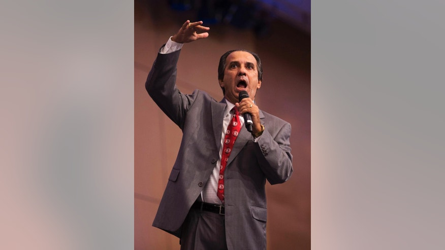 In this Sept.25, 2014 photo, Pastor Silas Malafaia gestures as he preaches during a service at the Assemblies of God church, in Rio de Janeiro Brazil. Malafaia backs top opposition candidate Marina Silva, who could become the first Pentecostal leader in the nation with more Catholics than any other, should she eventually defeat incumbent Dilma Rousseff, who now has a slight lead in polls looking at a likely runoff vote on Oct. 26. (AP Photo/Leo Correa)