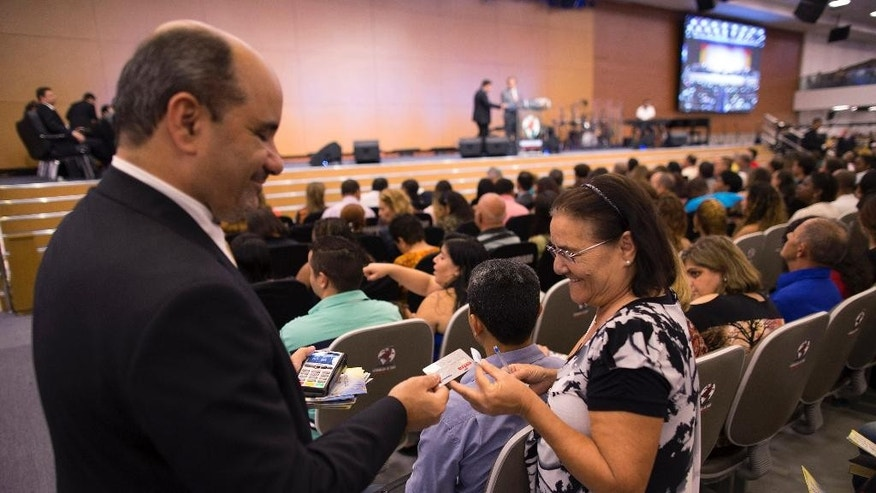 In this Sept.25, 2014 photo, a woman gives her contribution, using a credit card, to the Assemblies of God church, in Rio de Janeiro Brazil. When it comes time to cast their ballot, Brazilian Pentecostals, who are overwhelmingly poor, will face a dilemma in choosing between challenger Marina Silva, a woman who shares their faith, and their gratitude to incumbent President Dilma Rousseff's Workers Party for strong socio-economic advances in the last 12 years. (AP Photo/Leo Correa)