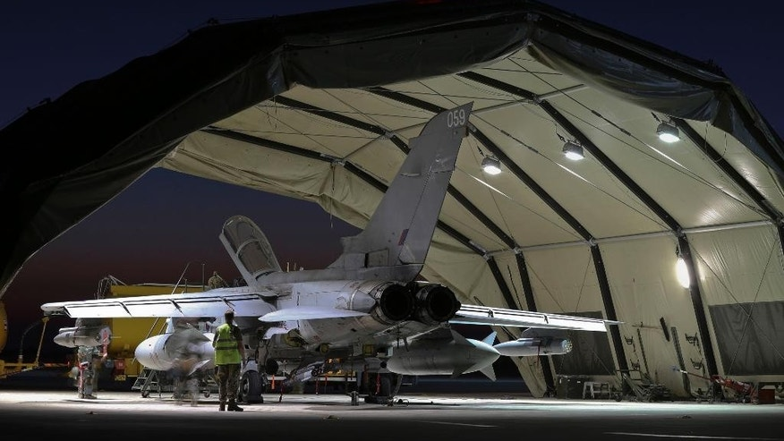 In this image released by Britain's Ministry of Defence a RAF Tornado is checked at RAF Akrotiri  in Cyprus after its from return armed mission in Iraq Tuesday Sept. 30, 2014. Britain's Ministry of Defence on Wednesday Oct. 1, 2014 said two RAF Tornados fired  missiles against an armed pick-up truck and transport vehicle west of Baghdad. It is the second time UK forces have hit Islamic State group targets  since the British  Parliament authorised involvement in the international military campaign last week. (AP Photo/Crp Neil Bryden RAF, MOD)