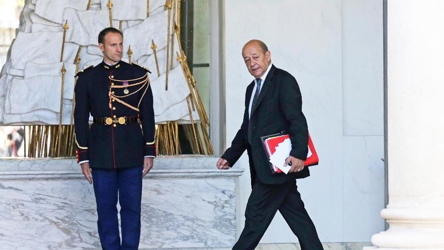 French Defense Minister Jean-Yves Le Drian walks in the lobby of the Elysee Palace on his way to a special defense meeting, on the country's mission against the Islamic State group, with French President Francois Hollande in Paris, Wednesday Oct. 1, 2014. (AP Photo/Remy de la Mauviniere)