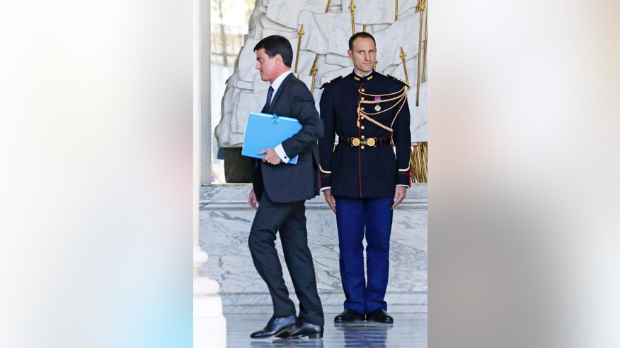 French Prime Minister Manuel Valls walks in the lobby of the Elysee Palace on his way to a special defense meeting, on the country's mission against the Islamic State group, with French President Francois Hollande in Paris, Wednesday Oct. 1, 2014. (AP Photo/Remy de la Mauviniere)