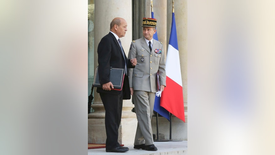 French Defense Minister Jean-Yves Le Drian, left, speaks with French Chief of Staff General Pierre de Villiers, as they leave the Elysee Palace following a special defense meeting,  on the country's mission against the Islamic State group, with French President Francois Hollande in Paris, Wednesday Oct. 1, 2014. (AP Photo/Remy de la Mauviniere)