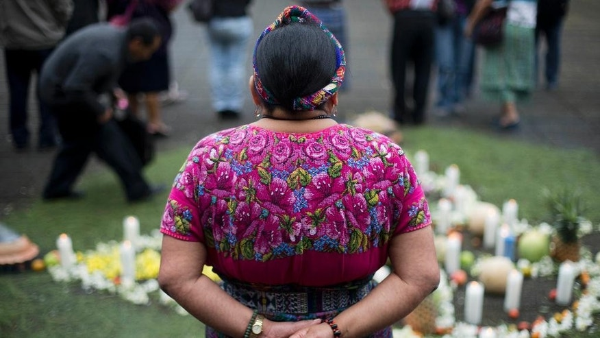 Rigoberta Menchu, a Nobel Peace prize winner, attends a religious Mayan ceremony outside the Supreme Court before the start of a trial connected to the death of her father in Guatemala City, Wednesday, Oct. 1, 2014. Former police chief Pedro Garcia Arredondo is going on trial for death of Menchu's father, and 36 more people, who died in a Jan. 31, 1980 attack by alleged government agents. The attackers burned down the Spanish embassy in Guatemala that Mayan peasants were occupying in protest. (AP Photo/Moises Castillo)