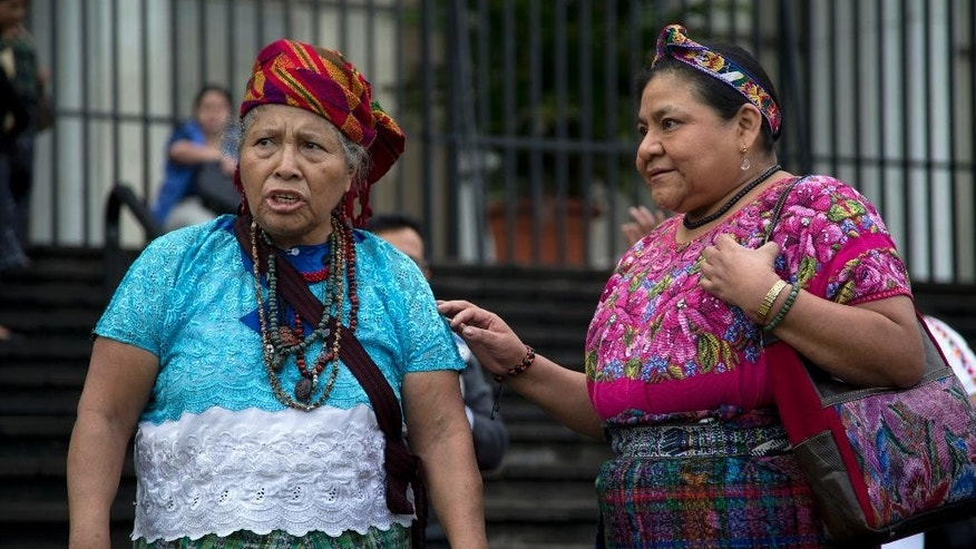 Rigoberta Menchu, a Nobel Peace prize winner, right, talks with Mayan priestess Juana Vasquez during a religious Mayan ceremony outside Supreme Court before the start of a trial involving the death of Menchu's father in Guatemala City, Wednesday, Oct. 1, 2014. Former police chief Pedro Garcia Arredondo is going on trial in connection with the death of Menchu's father, and 36 more people, who died in a Jan. 31, 1980 attack by alleged government agents. The attackers burned down the Spanish embassy in Guatemala where Mayan peasants were occupying in protest. (AP Photo/Moises Castillo)