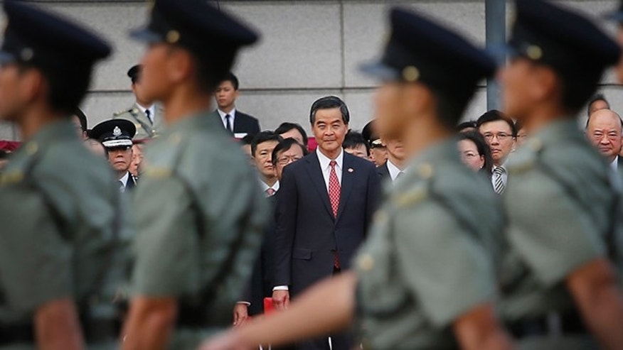 Oct. 1, 2014: Hong Kong's Chief Executive Leung Chun-ying, center, watches as military personnel march during a flag-raising ceremony, as thousands of protesters watching from behind police barricades yelled at him to step down. (AP)