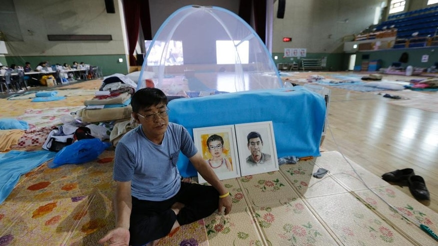 In this Sept. 11, 2014 photo, Kwon Oh-bok, a relative of the victims of the sunken ferry Sewol, speaks during an interview in front of portraits of his missing brother and nephew, at a gymnasium in Jindo, South Korea. Kwon lives in a tent in a dimly lit gym on Jindo island, the building where hundreds of families have received tragic news over the past six months. (AP Photo/Ahn Young-joon)