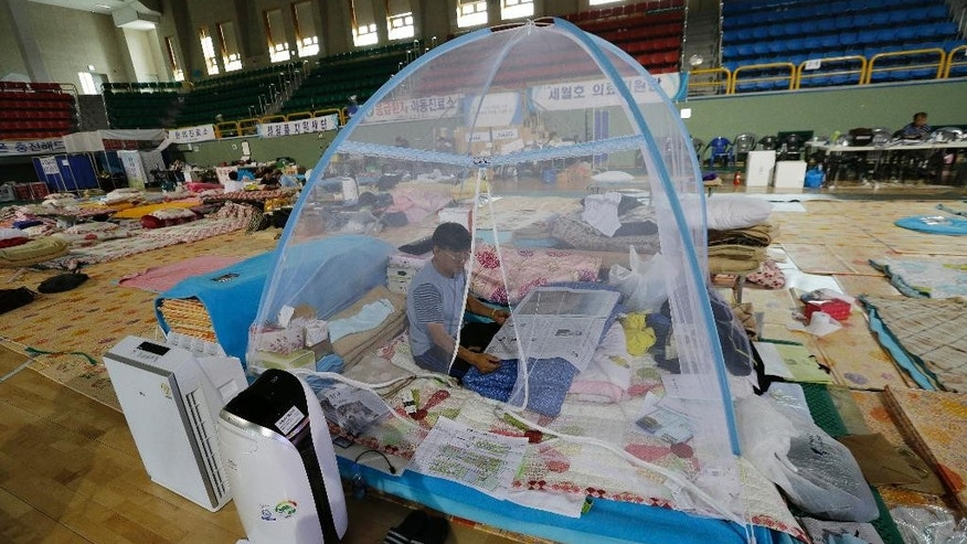 In this Sept. 11, 2014 photo, Kwon Oh-bok, a relative of the victims of the sunken ferry Sewol, reads newspapers at a gymnasium in Jindo, South Korea. Relatives of the 10 passengers still missing remain at the gym, a staging area for the families since the disaster began. Local officials have offered them better lodging, but the families have refused to leave. (AP Photo/Ahn Young-joon)
