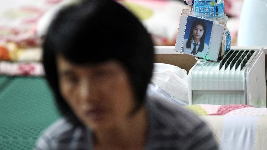 In this Sept. 11, 2014 photo, Park Eun-mi, a mother of Huh Da-yun, a missing passenger on board the ferry Sewol sank April 16, speaks during an interview at a gymnasium in Jindo, South Korea. In a dimly lit gym on Jindo island, hundreds of families have received tragic news over the past six months, and a tormented few still wait for it. (AP Photo/Ahn Young-joon)