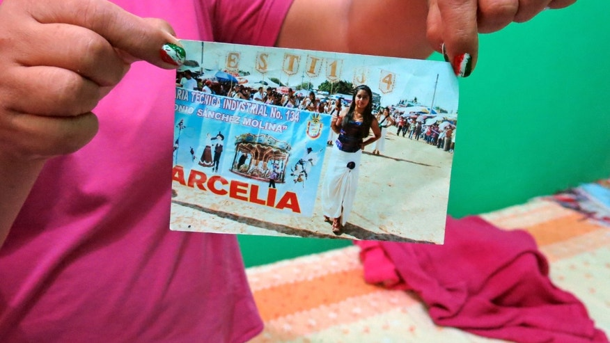 In this Sept. 15, 2014 photo, a woman who did not want to give her name for fear of reprisals, holds up a photograph of her late 15-year-old daughter Erika Gomez Gonzalez, at her home in Arcelia, Mexico. The woman says she witnessed her child's death when army soldiers fired first at an armed group at a grain warehouse on June 30 in the town of San Pedro Limon, Mexico. She said one man died in the initial shootout, when the rest of the gunmen surrendered on the promise they would not be hurt. She recalls that her daughter, who was face down in the ground with a bullet in her leg, was rolled over while she was still alive and shot more than half a dozen times in the chest. The mother said she arrived to the warehouse the day before the shooting, in an attempt to take her daughter home, but gang members wouldn't let her. (AP Photo/Eduardo Castillo)