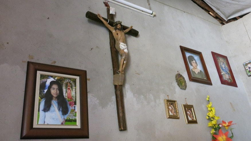In this Sept. 15, 2014 photo, a photograph of Erika Gomez Gonzalez, left, hangs on the wall of her mother's home in Arcelia, Mexico. Gomez's mother, who did not want to give her name for fear of reprisals, says she witnessed her daughter's death when army soldiers fired first at an armed group at a warehouse on June 30 in the town of San Pedro Limon, Mexico. She said one man died in the initial shootout, when the rest of the gunmen surrendered on the promise they would not be hurt. She recalled that her daughter, who was face down in the ground with a bullet in her leg, was rolled over while she was still alive and shot more than half a dozen times in the chest. The mother said she arrived to the warehouse the day before the shooting, in an attempt to take her daughter home, but gang members wouldn't let her. (AP Photo/Eduardo Castillo)