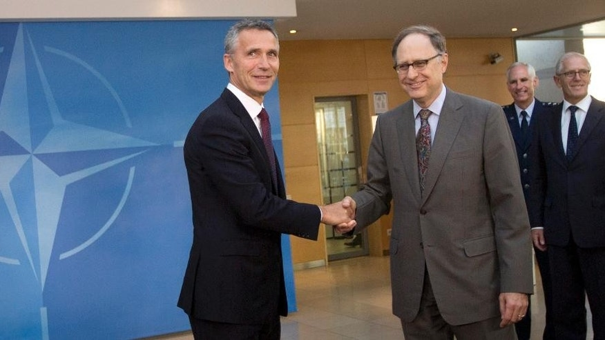 New NATO Secretary General Jens Stoltenberg, left, shakes hands with NATO Deputy Secretary General Alexander Vershbow as he arrives for his first day of work at NATO headquarters in Brussels on Wednesday, Oct. 1, 2014. A two-time prime minister, Stoltenberg became a recognizable face on the international scene with his dignified response to the twin terror attacks in Norway in July 2011. (AP Photo/Virginia Mayo)