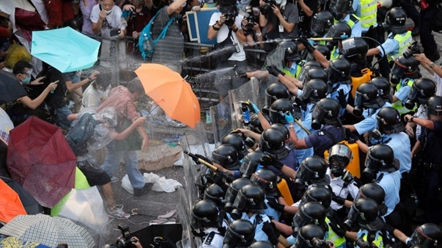 FILE - In this Sept. 28, 2014 file photo, riot police use pepper spray against protesters after thousands of people block a main road to the financial central district outside the government headquarters in Hong Kong. (AP Photo/Vincent Yu, File)