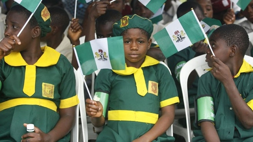 Oct. 1, 2014: School children wave Nigeria flags during the 54th anniversary celebrations of Nigerian independence