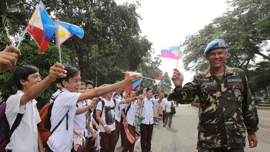 Students wave Philippine flags to cheer Filipino UN peacekeepers as they are given a heroes welcome Wednesday, Oct. 1, 2014, at Camp Aguinaldo in suburban Quezon city northeast of Manila, Philippines. In a separate ceremony at the Presidential Palace earlier, Philippine President Benigno Aquino III said his government will no longer deploy troops to security hotspots in the world where they can face unclear or impossible U.N. peacekeeping missions like in the Golan Heights, where Filipino forces came under attack by al-Qaida-linked insurgents. Aquino III said Wednesday hundreds of Filipino peacekeepers were tasked to guard a buffer zone separating Israel and Syria. But when the current Syrian conflict spilled over into the buffer zone and anti-government Islamic militants started attacking the Filipino peacekeepers, their mission became unclear and highly dangerous. (AP Photo/Bullit Marquez)