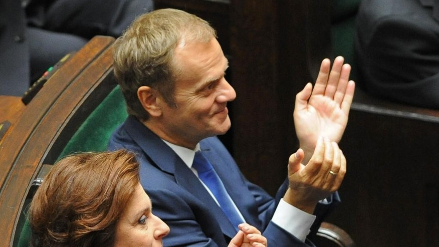 Former Polish Prime Minister Donald Tusk, right, applauds his successor Ewa Kopacz during her inaugural speech in the parliament in Warsaw, Poland, Wednesday, Oct. 1, 2014. Kopacz took over the post from Tusk, who will head the European Council starting Dec. 1. (AP Photo/Alik Keplicz)