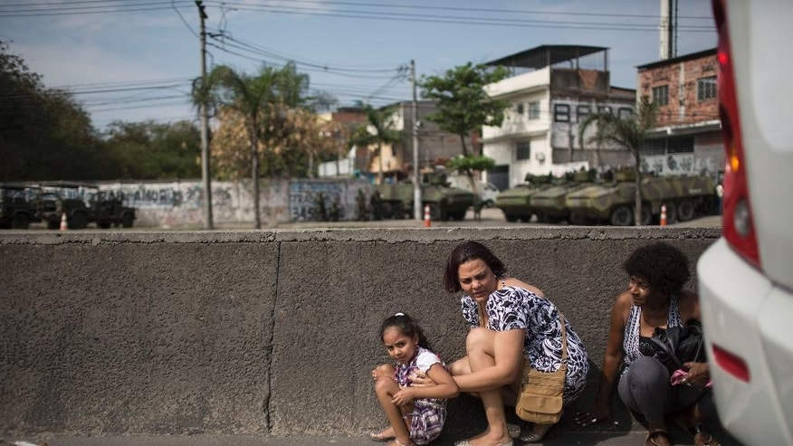 People take cover behind a concrete guardrail separating lanes on Avenida Brasil during a conflict between Brazilian Navy soldiers and alleged drug traffickers, near an entrance of Vila do Joao slum, part of the Complexo da Mare, in Rio de Janeiro, Brazil, Wednesday, Oct. 1, 2014. Pictured in the background are Navy armored vehicles and soldiers. (AP Photo/Felipe Dana)