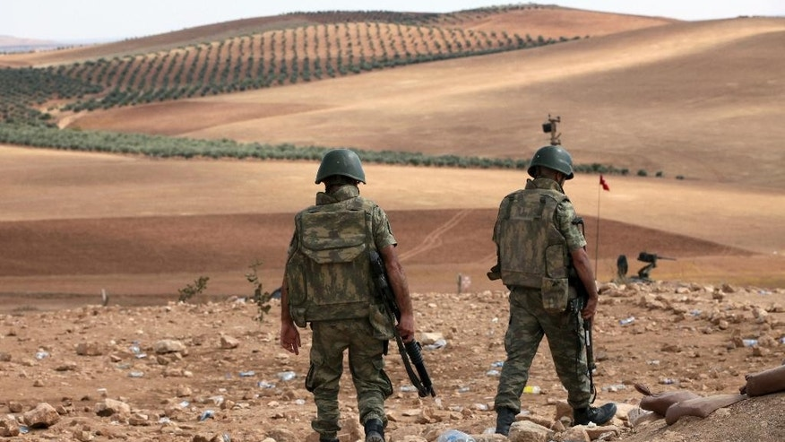 Turkish soldiers patrol as Islamic militants fight Kurdish forces to the west of Kobani, Syria, at the Turkey-Syria border near Suruc, Turkey, Tuesday, Sept. 30, 2014. U.S.-led coalition airstrikes targeted fighters, vehicles and artillery pieces of the Islamic State group on both sides of the Syria-Iraq frontier Tuesday, including around a beleaguered Kurdish town near the Syrian-Turkish border that is under assault by the militants, activists said.  (AP Photo/Burhan Ozbilici)