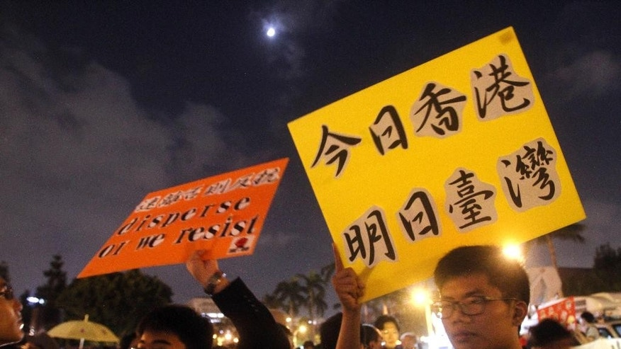 "Hong Kong and Taiwanese demonstrators hold slogan reading ""Hong Kong Today. Taiwan Tomorrow"" to support pro-democracy protests taking place in Hong Kong at the Liberty Square in front of Chiang Kai-shek Memorial Hall in Taipei, Taiwan, Wednesday, Oct. 1, 2014. (AP Photo/Chiang Ying-ying)"